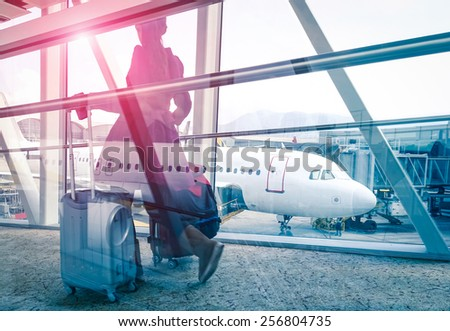Travel concept with woman and suitcase moving fast to airport terminal gate - Double exposure look with focus on the aircraft in the background - Violet marsala sun flare with vintage filtered editing - stock photo