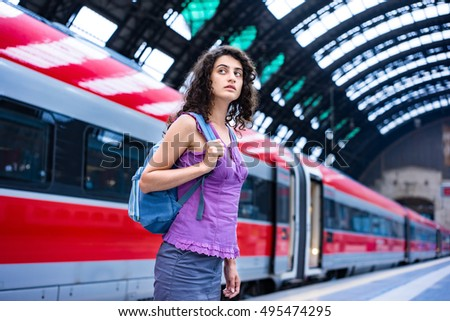Travel concept. Woman tourist on the train station platform. Tourist europe travel with backpack.