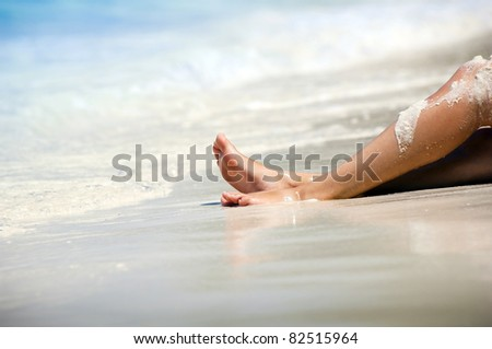 Travel concept - Womans legs on beautiful tropical beach with bright sand