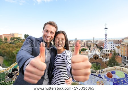 Travel couple happy in Park Guell, Barcelona, Spain. Beautiful young multiracial couple giving thumbs up hand sign smiling happy having fun on Europe vacation trip. Asian woman, Caucasian man. - stock photo