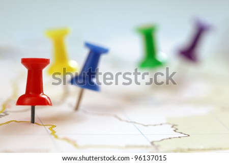Travel destination points on a map indicated with colorful thumbtacks and shallow depth of field with space for copy - stock photo