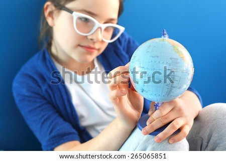 Travel dreams. The girl shows a finger on the globe   - stock photo