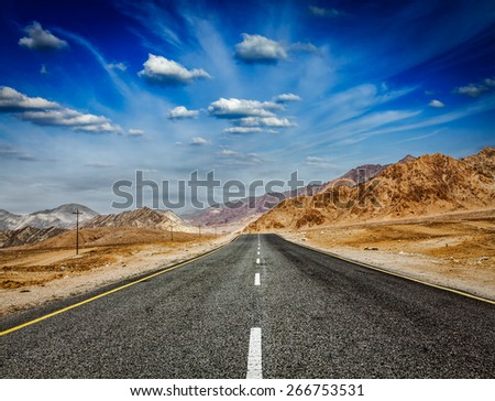 Travel forward concept background - road in Himalayas with mountains and dramatic clouds. Ladakh, Jammu and Kashmir, India - stock photo