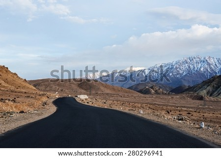 Travel forward concept background - road on plains in Himalayas with mountains. Manali-Leh road, Ladakh, Jammu and Kashmir, India - stock photo