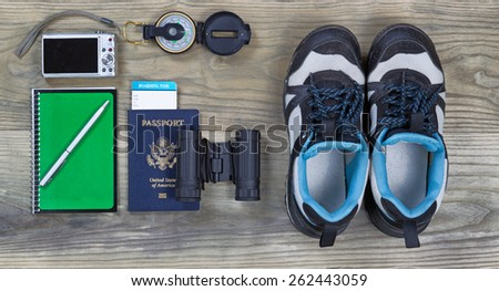 Travel gear basics on aged wooden surface - stock photo