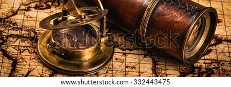 Travel geography navigation concept background - letterbox panorama of old vintage retro compass with sundial and spyglass on ancient world map - stock photo