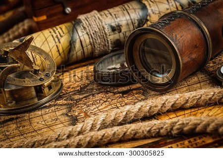 Travel geography navigation concept background - old vintage retro compass with sundial, spyglass and rope on ancient world map - stock photo