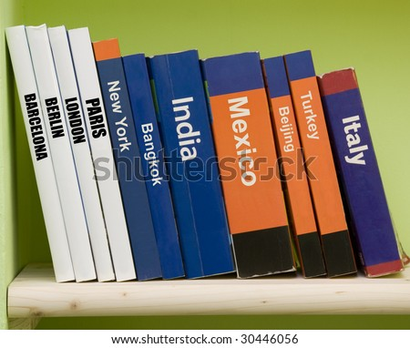 Travel guide books on a shelf - stock photo