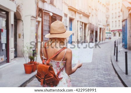 travel guide, tourism in Europe, woman tourist with map on the street - stock photo