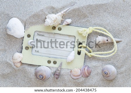 travel identification tag on sand with sea shells - stock photo