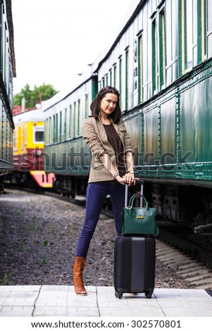travel in retro style. businesswoman on vacation near vintage passenger wagon on railway station