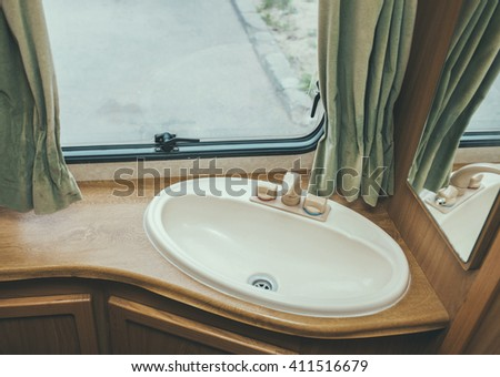 Travel in your home! Caravan interior trailer mobile home- sink, window, mirror and curtains - stock photo