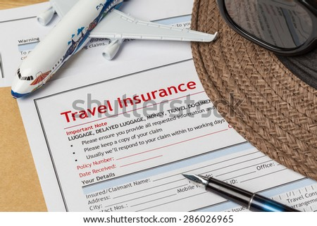 Travel Insurance Claim application form and hat with eyeglass and pen on brown envelope, business insurance and risk concept; document and plane is mock-up