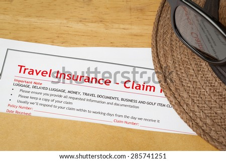 Travel Insurance Claim application form and hat with eyeglass on brown envelope, business insurance and risk concept; document is mock-up