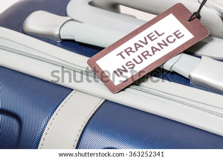 Travel insurance label tied to a suitcase.