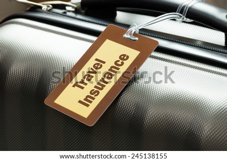 Travel insurance luggage tag tied to a suitcase - stock photo