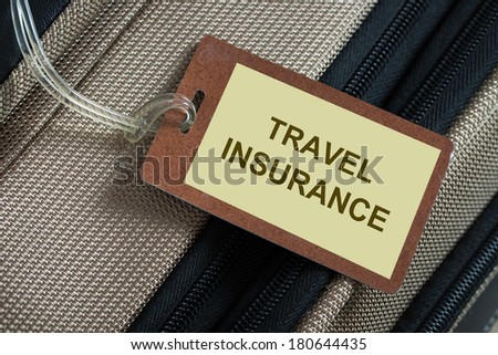 Travel insurance tag tied to a luggage - stock photo
