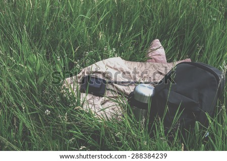 Travel kit - backpack, thermos and camera on the grass - stock photo
