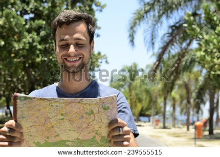 travel lifestyle: male tourist with map  - stock photo