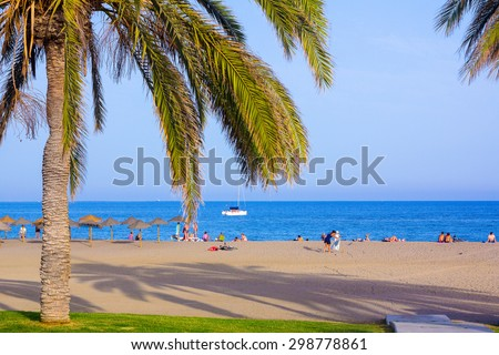 Travel Malagueta beach with palm trees and blue sea in Malaga Spain - stock photo