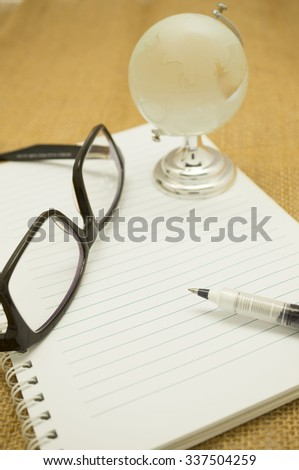 Travel notes concept, blank notes, pen and crystal globe - stock photo