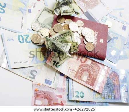 Travel on vacation lifestyle concept: cash money on table in mess with passport and change - stock photo