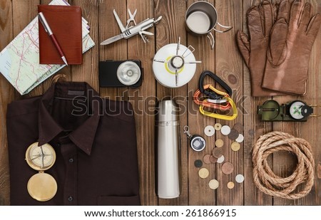 Travel. Overhead view of hiking gear laid out for a backpacking trip on a rustic wood floor. Items include, rope, gloves, sweater, carabiners  book, belt, cup, passport, wallet, canteen, compass - stock photo