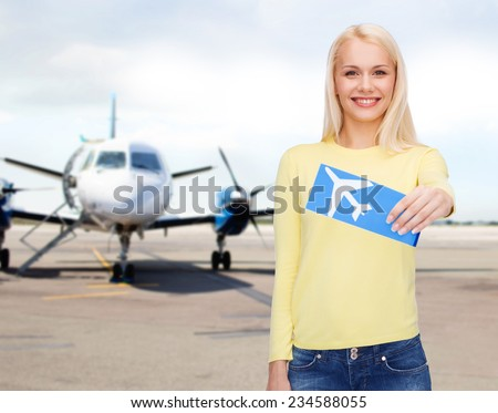 travel, people and transportation concept - smiling young woman with airplane ticket at airport - stock photo