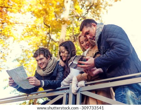 travel, people, tourism, and friendship concept - group of smiling friends with map and city guide standing on bridge in city park - stock photo