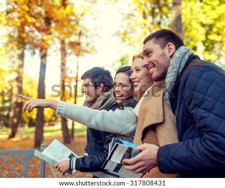 travel, people, tourism, gesture and friendship concept - group of smiling friends with map standing on bridge and pointing finger in city park