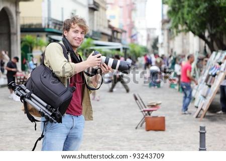 Travel photographer, Havana, Cuba on Plaza de Armas in Old Havana with Camera equipment taking pictures. - stock photo