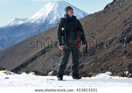 Travel photographer hike the Tongariro crossing with Mount Ngauruhoe  and Mount Tongariro at the background in Tongariro National Park at the center of New Zealand's North Island - stock photo
