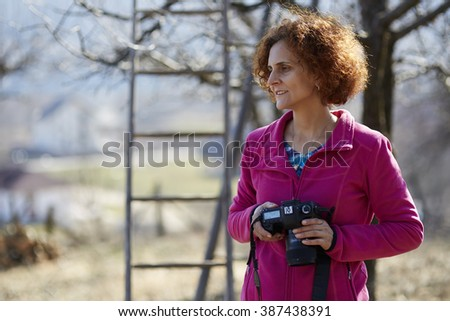Travel photographer woman with her camera taking photos in the countryside