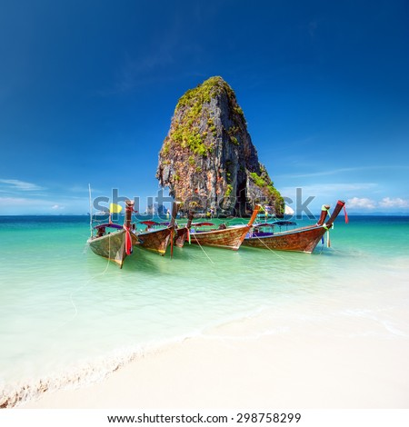 Travel photography of wooden boats on shore of tropical sea with scenic rock mountain in water. Vacation journey background of Thailand nature  - stock photo