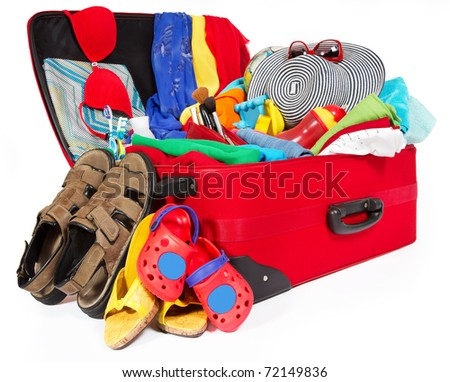 Travel red suitcase. Packed for vacation in sea resort. Family personal belongings: slippers, sandals, hat, towel. Isolated on white - stock photo