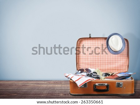 Travel. Retro tourist luggage with colorful clothes and copyspace on grungy background - stock photo