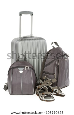 Travel set consisting of the silver travel suitcase, two gray backpacks and travel shoes, isolated on white background