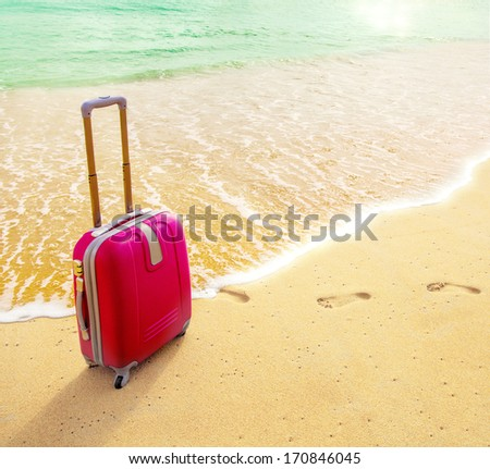 Travel suitcase is alone on a beach with the lake or ocean in the background. - stock photo