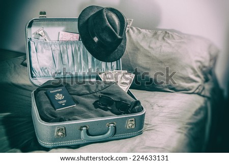 Travel Suitcase Man Vacation. Suitcase on a bed with vintage man's clothes edited with a vintage photograph filter. - stock photo