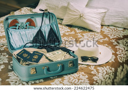 Travel Suitcase Woman Vacation. Suitcase on a bed with women's clothes and a tropical theme and a vintage photograph filter. - stock photo