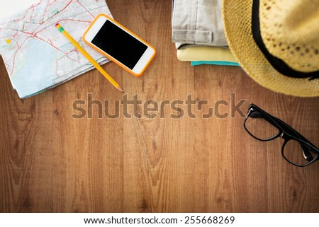 travel, summer vacation, tourism and objects concept - close up of folded clothes, smartphone and touristic map on wooden table - stock photo
