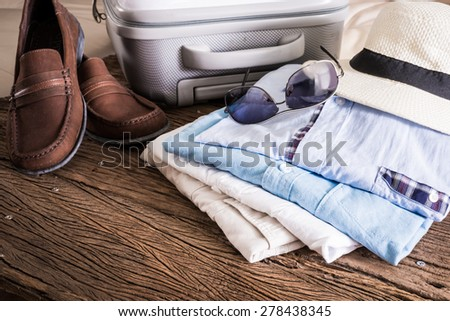 travel, summer vacation, tourism and objects concept, close up of folded clothes, smartphone and sunglasses, leather shoes on wooden table - stock photo