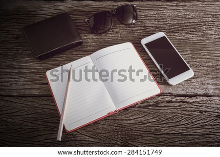 travel, summer vacation, tourism and objects concept. close up of notebook, pencil, wallet, smartphone and sunglasses on wooden table. Photo retro style - stock photo