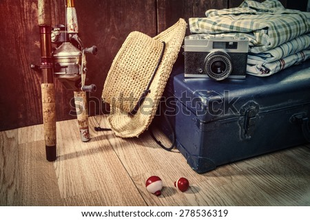 Travel theme still life with vintage items and fishing poles - stock photo