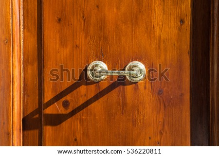 travel to Italy - old external brass door handle on brown wooden door in Rome city
