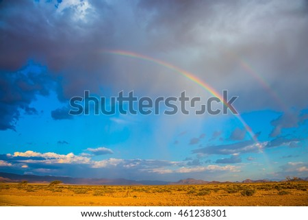 Travel to Namibia. Magnificent rainbow crossed the sky over the desert. Dirt road in the African steppe. The concept of exotic tourism