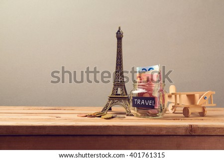 Travel to Paris, France concept with Eiffel Tower souvenir and wooden airplane toy. Planning summer vacation, money budget trip concept. - stock photo