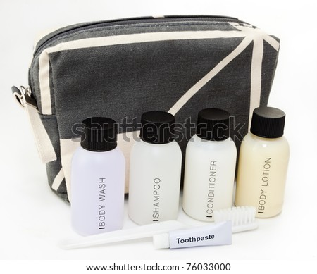 Travel toiletries kit in front of a small toiletries bag - stock photo