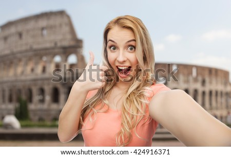 travel, tourism, emotions, expressions and people concept - happy smiling young woman taking selfie and showing thumbs up over coliseum background - stock photo