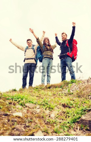 travel, tourism, hike, gesture and people concept - group of smiling friends with backpacks raising hands outdoors - stock photo